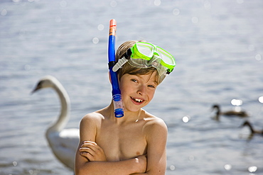 A young boy with a scuba mask in front of a lake