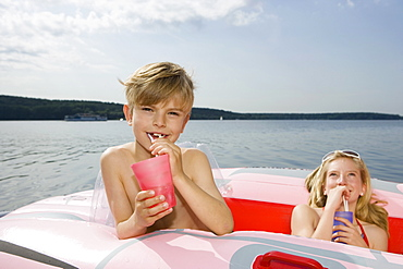Two children in an inflatable raft on a lake