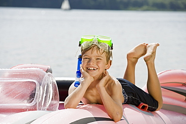 A young boy lying on an inflatable raft on a lake