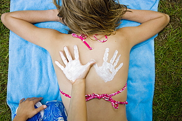 A girl with a suntan lotion handprint on her back and a boy's hand next to it