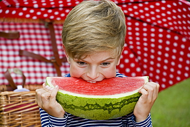 A young boy eating a slice of watermelon