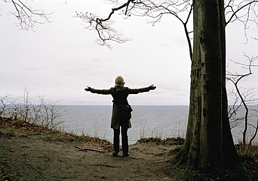 A woman with her arms outstretched facing the sea