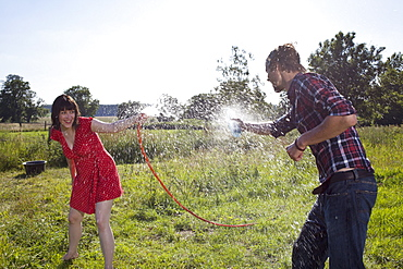 Man and woman spray each other with water in field