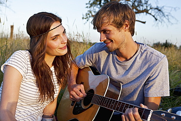 Man plays guitar to his girlfriend in field