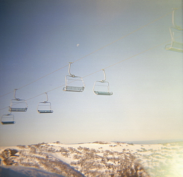 A ski lift above snow-capped mountains