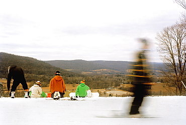 Rear view of snowboarders sitting at the edge of a ski slope