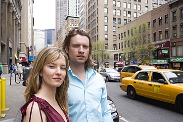 A young couple standing on a city street, new york city