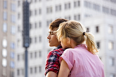 A young couple embracing in an urban setting