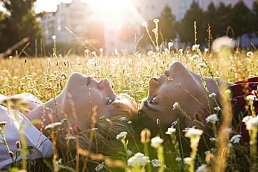 A young couple lying in on their backs in grass, close-up