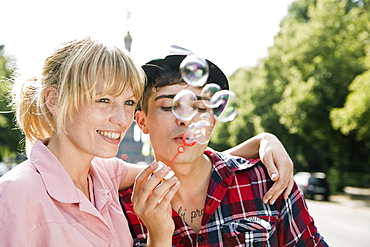 A young couple blowing bubbles
