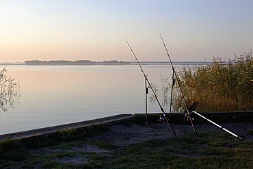 Two fishing rods on an embankment