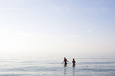 Two people standing in the sea