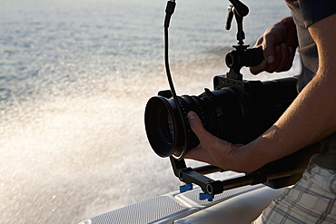 A cameraman filming on a motorboat