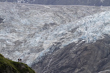 Two hikers looking at a glacier