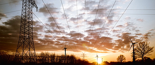 Electricity pylons and wind turbines against cloudy sky at dusk