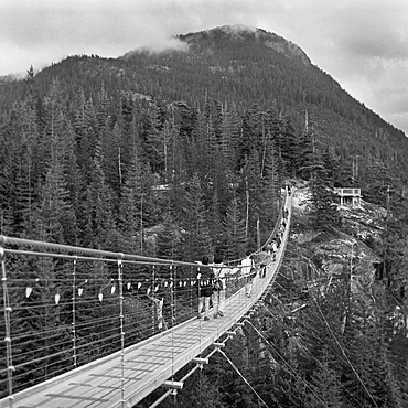People walking on footbridge leading towards mountain