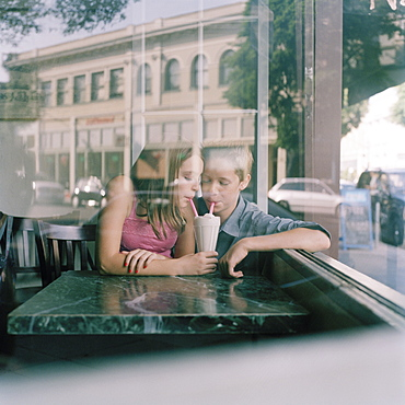 A young teenage couple sharing a milkshake at a diner, viewed through window