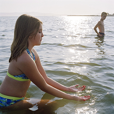 A teenage girl scooping on water while wading in the sea