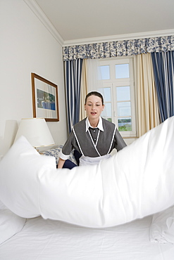 Uniformed maid making bed in hotel room