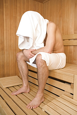 Young man in a sauna with towel over head