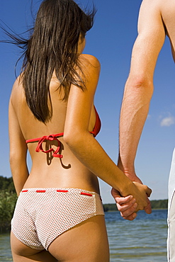 Young couple holding hands in front of lake