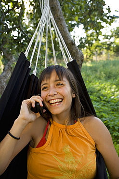 Young woman sitting in hammock and talking on mobile phone