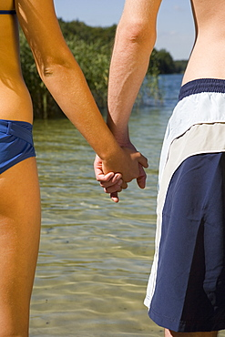 Close-up of couple holding hands in front of lake