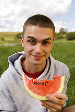 Portrait of young man eating watermelon