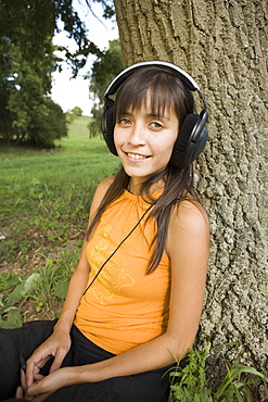 Young woman sat below tree listening to music