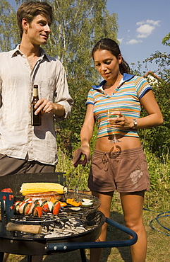 Young couple cooking food on barbeque grill