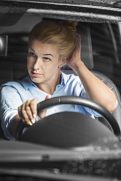 Mid adult woman looking at herself in rear-view mirror while driving car