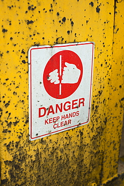Warning sign on yellow wall outdoors