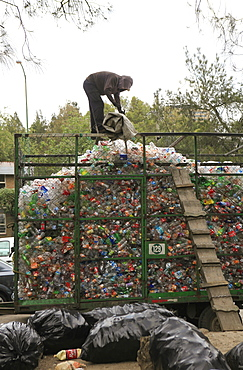 Man working on heap of recyclable plastic waste at garbage dump