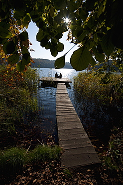 Two people sitting at the end of a jetty, silhouetted