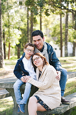 Portrait of happy family sitting on picnic table in forest
