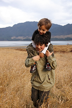 A teenage boy carrying his younger brother on his shoulders