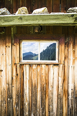 Full frame shot of log cabin with reflection of mountains on window