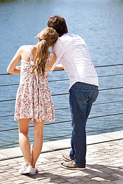 A young couple standing at a railing enjoying the lake view