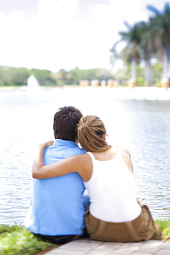 An affectionate couple sitting by a lake, rear view