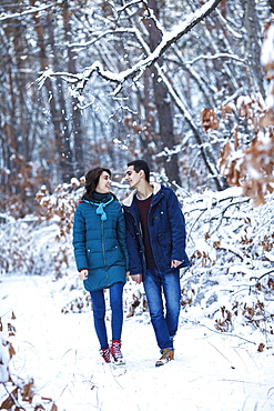 Full length of loving young couple in warm clothing walking on snowy field