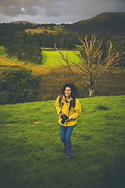 High angle view of happy woman with camera on grassy hill