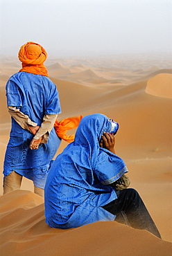 Moroccan men dressed in traditional clothing relaxing at Erg Chebbi desert, Morocco