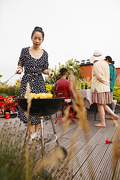 Young woman barbecuing corns while standing on patio with friends in background
