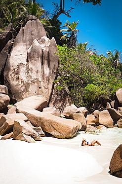 Side view of mid adult woman in bikini relaxing at beach, Island of La Digue, Seychelles