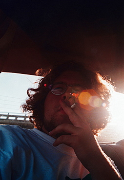 a young man smoking a cigarette in a car