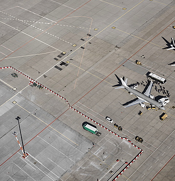 Aerial view of passengers boarding commercial airplane on tarmac at airport