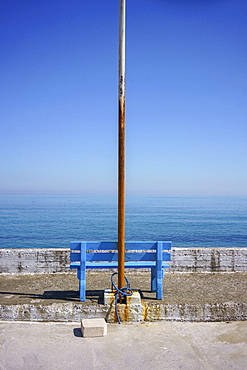 Rusted flagpole and blue bench with scenic ocean view, Kalyves, Crete, Greece