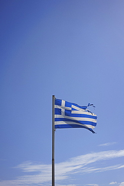 Ripped Greek flag blowing in wind against sunny blue sky