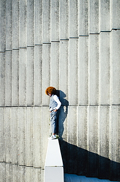 View from above young man with afro laying on sunny urban steps