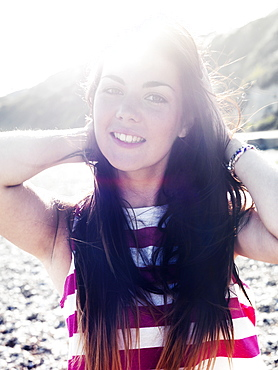 A young woman smiling cheerfully while at the beach